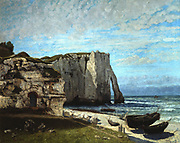 The Cliff at Etretat After the Storm',  Oil on canvas, 1870. Gustave Courbet (1819-1877) French Realist painter and designer.  Chalk cliff with natural arch, fishing boats drawn up on the beach, blue door into cliff .   Etretat, a small town 10 miles (16km) north of Le Havre,  on the coast of Normandy.