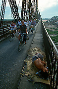 Long Bien Bridge across the Red River. Morning bicycle rushhour into the city. Man sleeping on the sidewalk.