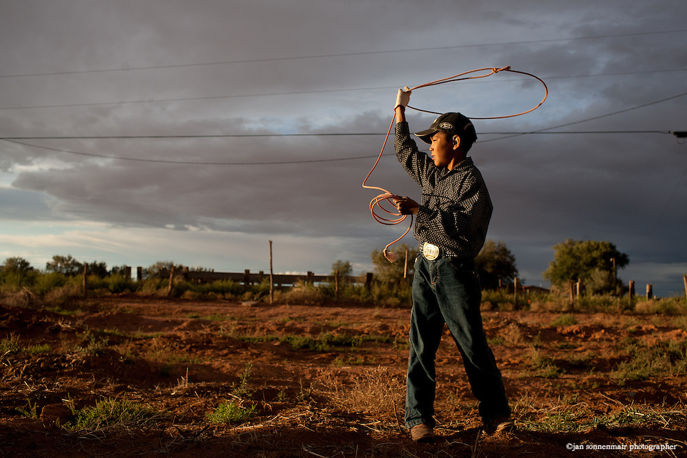A young Navajo boy practices with his lasso, or rope for calf roping in the rodeo