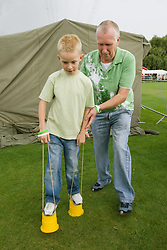 Grandfather helping grandson to learn to walk with foot walkers at a Parklife summer activities event,