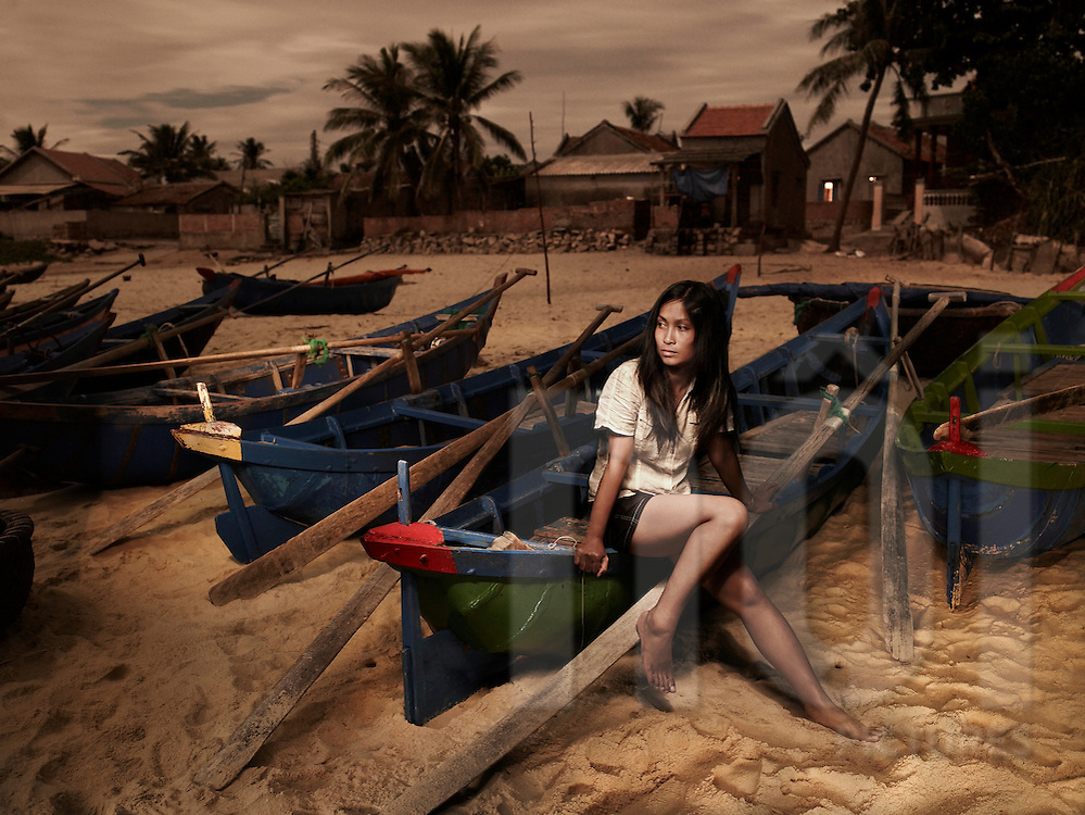 Portrait of a Vietnamese woman sitting on a wooden boat on shore thoughtfully looking out to sea, Phan Thiet, Vietnam, Southeast Asia