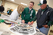 From left: Karen Peden, Don Peden III, and Don Peden Jr., all visiting from Texas, peruse materials from the Ohio University Archives collections, which were on display on the fourth floor of Alden Library for Homecoming Weekend on Saturday, Oct. 13, 2012. Ohio University's Peden Stadium was named after Don Peden Jr.'s father. (Photo by Lauren Pond/Ohio University Libraries)