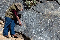 A guide points out Petroglyphs, Titus Canyon Road, Death Valley National Park, California, United States of America