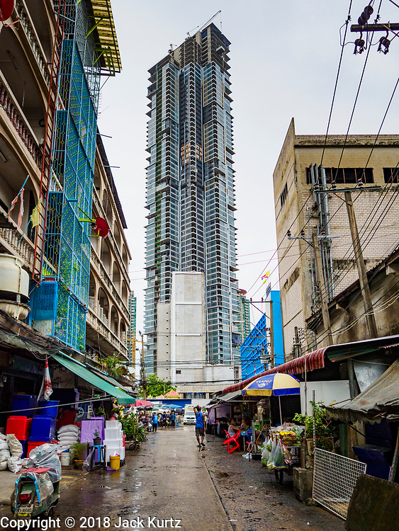 19 JULY 2018 - BANGKOK, THAILAND: A deluxe tourist hotel and condominium development under construction next to the Saphan Pla Fish Market in Bangkok. Fish consumption recently hit a record high according to a report published recently by the United Nations Food and Agriculture Organization. The FAO reported that global fish production peaked at about 171 million tonnes in 2016, 47 percent of it from fish farming. The FAO also reported that global fish consumption between 1961 and 2016 was rose nearly twice as fast as population growth. In 2015, fish accounted for about 17 percent of the animal protein consumed globally. This has ramifications for Thailand, which has one of the world's largest fish and seafood industries. About 90% of Thailand's seafood production is exported, which accounts for about 4% of Thailand's exports.       PHOTO BY JACK KURTZ