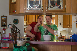1/27/15 1:36:22 PM -- Louisa, KY, U.S.A  -- Cheryl Castle, left, makes a cake with her son Nate at her mother's house on Tuesday. Castle is a recent recipient of the high-tech device, can now do many tasks she was unable to do when her epileptic seizures became more severe and more frequent. Now she's getting back to a normal life.<br /> <br />  --    Photo by Jonathan Palmer, Freelance