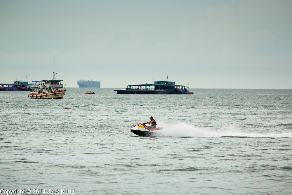 "26 SEPTEMBER 2014 - PATTAYA, CHONBURI, THAILAND:  Tourists ride a personal watercraft in the Gulf of Siam, off of Pattaya Beach. Pataya, a beach resort about two hours from Bangkok, has wrestled with a reputation of having a high crime rate and being a haven for sex tourism. After the coup in May, the military government cracked down on other Thai beach resorts, notably Phuket and Hua Hin, putting military officers in charge of law enforcement and cleaning up unlicensed businesses that encroached on beaches. Pattaya city officials have launched their own crackdown and clean up in order to prevent a military crackdown. City officials have vowed to remake Pattaya as a ""family friendly"" destination. City police and tourist police now patrol ""Walking Street,"" Pattaya's notorious red light district, and officials are cracking down on unlicensed businesses on the beach.    PHOTO BY JACK KURTZ"