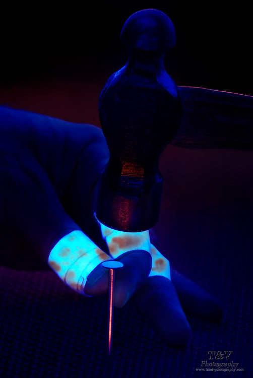 A hand with fingers covered by glowing bandages holds a nail as a hammer is about to strike it.Black light