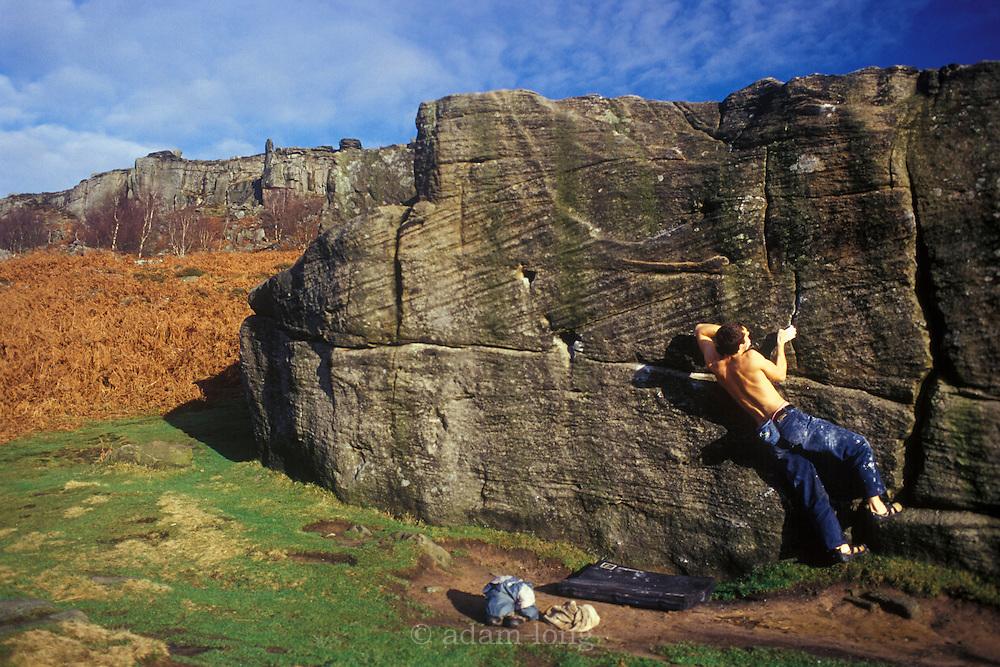 Joe Bawden bouldering on the Trackside boulder, Curbar