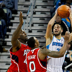 January 29, 2012; New Orleans, LA, USA; New Orleans Hornets point guard Greivis Vasquez (21) is defended by Atlanta Hawks forward Ivan Johnson (44) and point guard Jeff Teague (0) during a game at the New Orleans Arena. The Hawks defeated the Hornets 94-72.  Mandatory Credit: Derick E. Hingle-US PRESSWIRE