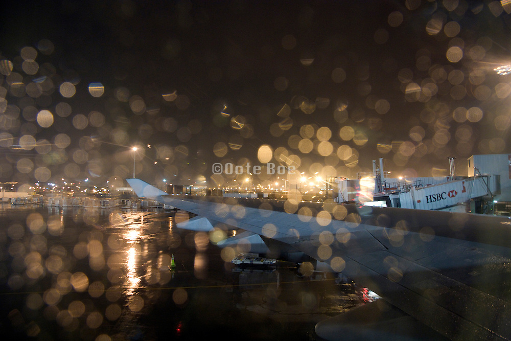 with raindrops covered passenger airplane window looking out of the airport JFK