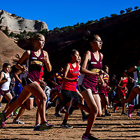 Girls varsity racers spring off the starting line during the Gallup Invitational Saturday at Red Rock Park in Gallup.