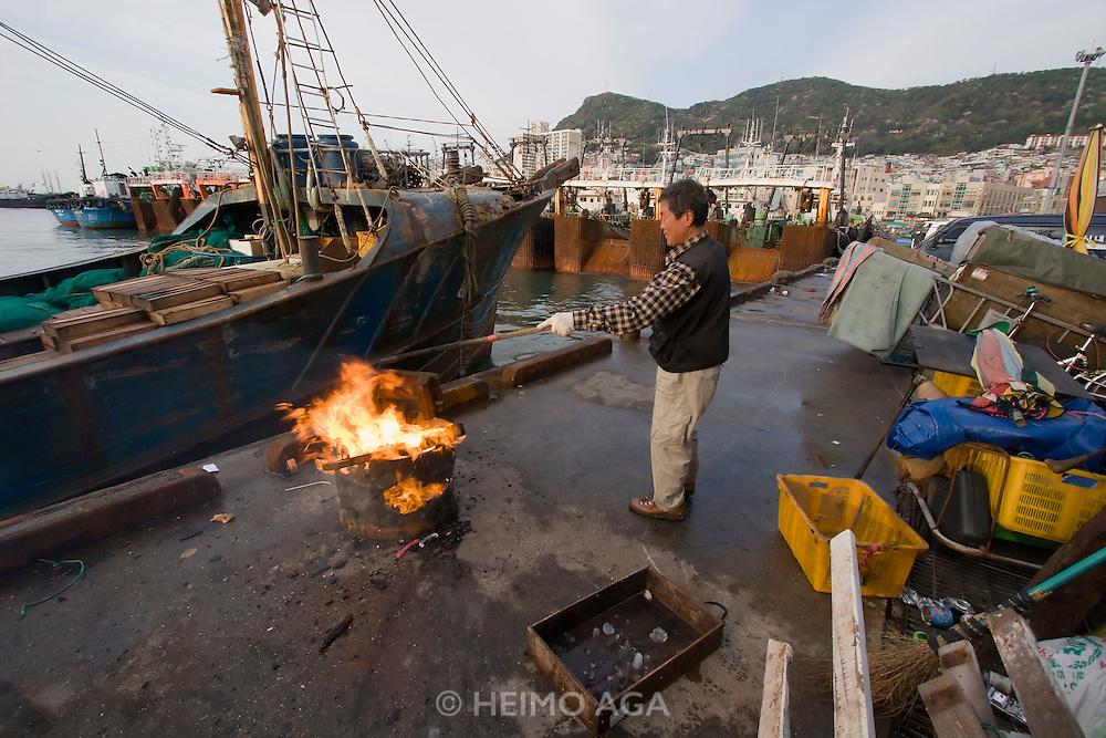 Jagalchi Fish Market. Man burning trash.