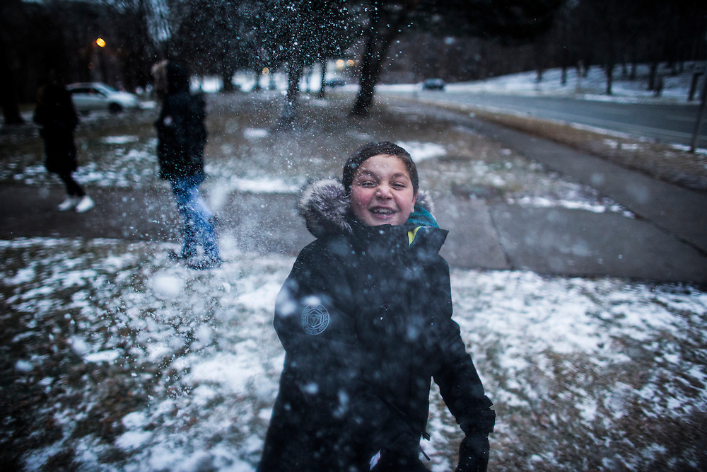 Syrian refugee Nasimi Batal Al Hasan plays in the snow outside of their apartment building in Mississauga, Ontario, Canada, Thursday January 21, 2016.   (Mark Blinch for the BBC)