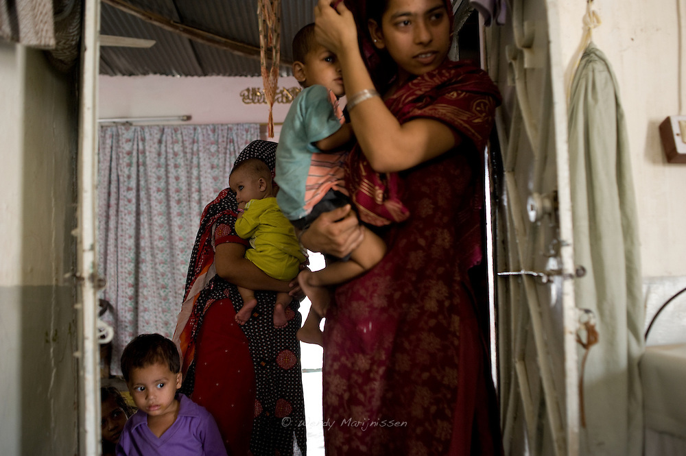 After the home delivery in the sleeping quarters is finished, Tara's family members open the door of their private living quarters and have a look. Karachi, Pakistan, 2011