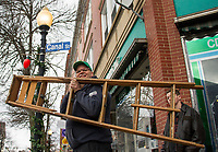 Jim and Nate Daubenspeck decorate downtown Laconia with garland and wreaths for the holiday season with Celebrate Laconia Saturday afternoon.  (Karen Bobotas/for the Laconia Daily Sun)