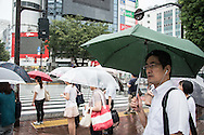 People waiting at the red light under the rain. Typhoon number 10 called Lionrock hit japan early on morning, in Tokyo. 30/08/2016-Tokyo, JAPAN