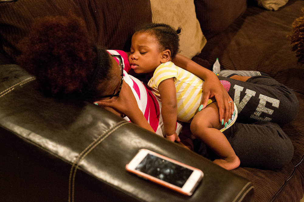 "Zayden Lowe, 10 months, finally passes out in his mother Alexis Lowe's arms at about 11 p.m. after fighting off sleep for an hour Tuesday, May 24, 2016, at their home on Grand Rapids' south side. Lowe said she is excited to graduate and is grateful for her support system throughout senior year. ""I did it more so for Zayden than I did for myself because Zayden needs me to grow up so he can be the man he'll be. So, what I do will affect what happens to him,"" she said. ""Me graduating on time is an accomplishment for both of us."""
