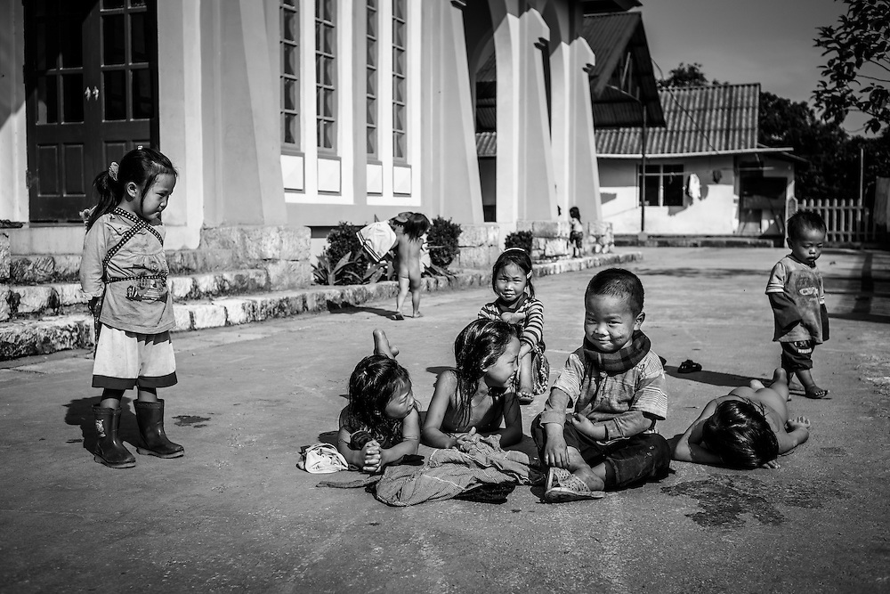 Ethnic minority children play and sunbathe in on the grounds of a church just outside Sapa, Vietnam.