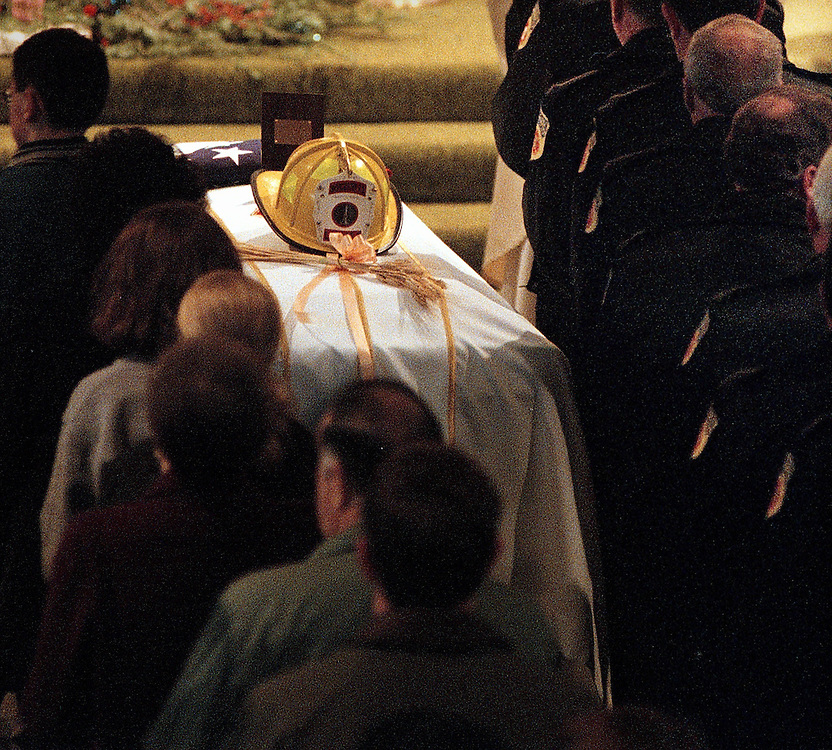 TGFIRE  Mourners pass by the casket of Thomas E. Spencer as they receive communion at St. Charles Boromeo Church. Shoot date 12/15/99