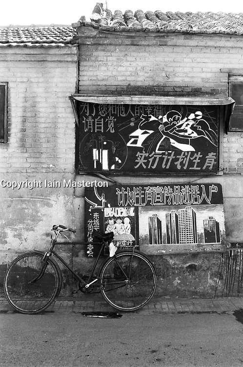 Blackboard chalked with family planning slogans and advice on wall in a Beijing hutong