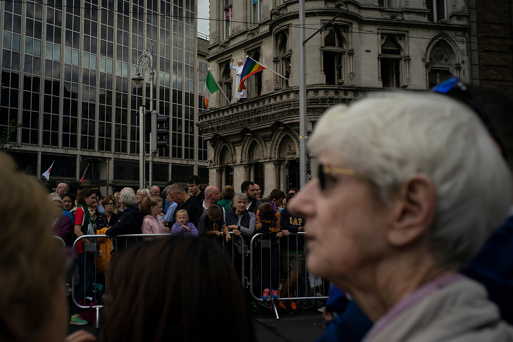 A figure of Pope Francis on a window ledge of Dublin's National Wax Museum, flanked by Irish and rainbow flags, as people await for the pope to pass by during the first day of a visit to Ireland.