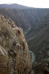 View of the Black Canyon and the Gunnison River from the Pulpit Rock Overlook off the South Rim Road.  Black Canyon of the Gunnison National Park is a United States National Park located near Montrose, Colorado in the western part of the state. The park is managed by the National Park Service. There are two entrances to the park; the more-developed south rim entrance is located 15 miles (24 km) east of Montrose, while the north rim entrance is located 11 miles (18 km) south of Crawford and is closed in the winter. The park contains 12 miles of the 48 mile long canyon of the Gunnison river. The park contains the deepest and most dramatic section of the canyon, one of the deepest mountain descents in North America.  The canyon continues upstream into the Curecanti National Recreation Area and downstream into the Gunnison Gorge National Conservation Area.