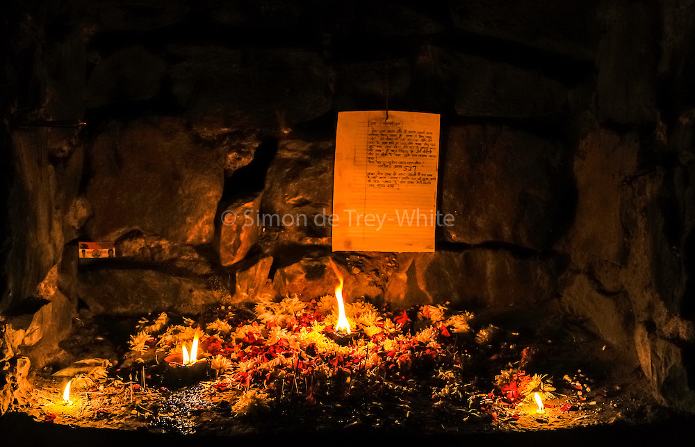 "17th December 2015, New Delhi, India. A photocopied wish with oil lamps and candles at a shrine dedicated to Djinns in the ruins of Feroz Shah Kotla in New Delhi, India on the 17th December 2015<br /> <br /> PHOTOGRAPH BY AND COPYRIGHT OF SIMON DE TREY-WHITE a photographer in delhi<br /> + 91 98103 99809. Email: simon@simondetreywhite.com<br /> <br /> People have been coming to Firoz Shah Kotla to pray to and leave written notes and offerings for Djinns in the hopes of getting wishes granted since the late 1970's. Jinn, jann or djinn are supernatural creatures in Islamic mythology as well as pre-Islamic Arabian mythology. They are mentioned frequently in the Quran  and other Islamic texts and inhabit an unseen world called Djinnestan. In Islamic theology jinn are said to be creatures with free will, made from smokeless fire by Allah as humans were made of clay, among other things. According to the Quran, jinn have free will, and Ibl?s abused this freedom in front of Allah by refusing to bow to Adam when Allah ordered angels and jinn to do so. For disobeying Allah, Ibl?s was expelled from Paradise and called ""Shay??n"" (Satan).They are usually invisible to humans, but humans do appear clearly to jinn, as they can possess them. Like humans, jinn will also be judged on the Day of Judgment and will be sent to Paradise or Hell according to their deeds. Feroz Shah Tughlaq (r. 1351–88), the Sultan of Delhi, established the fortified city of Ferozabad in 1354, as the new capital of the Delhi Sultanate, and included in it the site of the present Feroz Shah Kotla. Kotla literally means fortress or citadel."