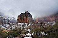 Dark clouds overshadow a snow covered river bed, Zion National Park