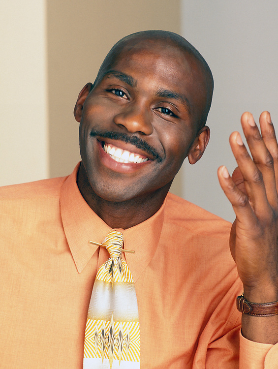 Portrait of Mid 30's African American Man smiling and gesturing with his hand.<br />