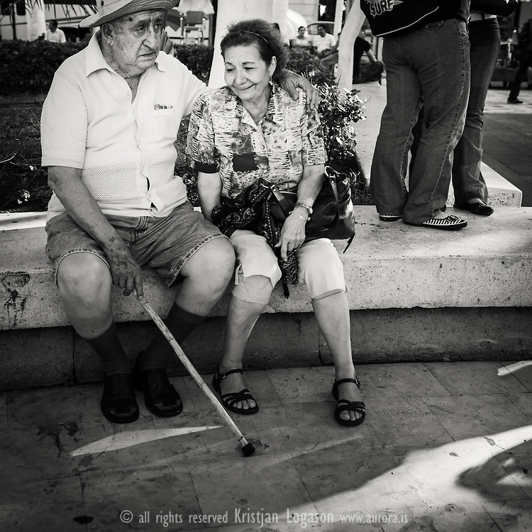Woman laughing while the man seems sad where thay sit on a stone bench at one of the central squers in Veracruz Mexico