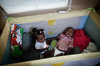 "HAL FAR, MALTA - JUNE 21: Two 15 months twins, children of Michael (25 years old from Ethiopia) cry in their crib in a Swiss Red Cross tent in the Hangar Open Center in Hal Far (which translates as ""Rat's Town"") on June 21, 2011. Michael and his wife left Libya on a boat that got lost in sea for 10 days, with no food nor water. They fed their twins with toothpaste and sea water for the entire trip. Michael's friend, Mubak (23 years old from Ethiopia), said  military planes and ships saw them on the second and sixth day. On the 10th day they set their boat on fire in order to get rescued. That's when the Maltese forces noticed them. A pregnant woman died on the 10th day, a few hours before the other passengers were rescued.<br /> <br /> The Hangar Open Center is a field with an ex-aircraft hangar which includes Swiss Red Cross tents in a dark, non lit space, and external containers. The conditions are very poor and the has inflamable oil on the floor.<br /> <br /> The Open Centres in Malta serve as a temporary accomodation facility, but they ended becoming permanent accomodation centres, except for those immigrants who receive subsidiary protection or refugee status and that are sent to countries such as the United States, Germany, Poland, and others. All immigrants who enter in Malta illegally are detained. Upon arrival to Malta, irregular migrants and asylum seekers are sent to one of three dedicated immigration detention facilities. Once apprehended by the authorities, immigrants remain in detention even after they apply for refugee status. detention lasts as long as it takes for asylum claims to be determined. This usually takes months; asylum seekers often wait five to 10 months for their first interview with the Refugee Commissioner. Asylum seekers may be detained for up to 12 months: at this point, if their claim is still pending, they are released and transferred to an Open Center.<br /> <br /> <br /> Gianni Cipriano for The New York Times"