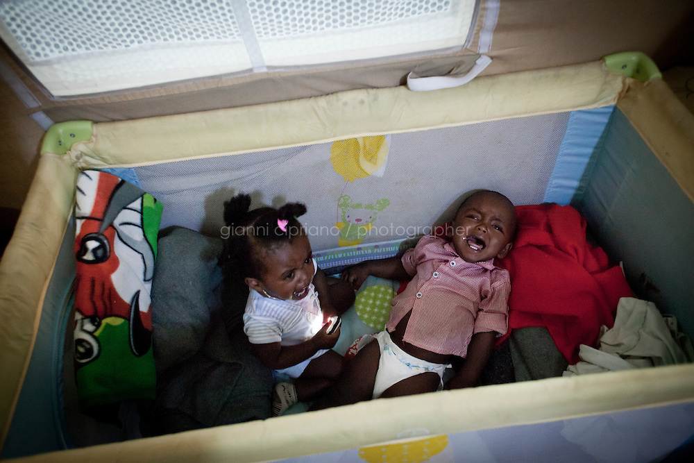 HAL FAR, MALTA - JUNE 21: Two 15 months twins, children of Michael (25 years old from Ethiopia) cry in their crib in a Swiss Red Cross tent in the Hangar Open Center in Hal Far (which translates as &quot;Rat's Town&quot;) on June 21, 2011. Michael and his wife left Libya on a boat that got lost in sea for 10 days, with no food nor water. They fed their twins with toothpaste and sea water for the entire trip. Michael's friend, Mubak (23 years old from Ethiopia), said  military planes and ships saw them on the second and sixth day. On the 10th day they set their boat on fire in order to get rescued. That's when the Maltese forces noticed them. A pregnant woman died on the 10th day, a few hours before the other passengers were rescued.<br /> <br /> The Hangar Open Center is a field with an ex-aircraft hangar which includes Swiss Red Cross tents in a dark, non lit space, and external containers. The conditions are very poor and the has inflamable oil on the floor.<br /> <br /> The Open Centres in Malta serve as a temporary accomodation facility, but they ended becoming permanent accomodation centres, except for those immigrants who receive subsidiary protection or refugee status and that are sent to countries such as the United States, Germany, Poland, and others. All immigrants who enter in Malta illegally are detained. Upon arrival to Malta, irregular migrants and asylum seekers are sent to one of three dedicated immigration detention facilities. Once apprehended by the authorities, immigrants remain in detention even after they apply for refugee status. detention lasts as long as it takes for asylum claims to be determined. This usually takes months; asylum seekers often wait five to 10 months for their first interview with the Refugee Commissioner. Asylum seekers may be detained for up to 12 months: at this point, if their claim is still pending, they are released and transferred to an Open Center.<br /> <br /> <br /> Gianni Cipriano for The New York Times