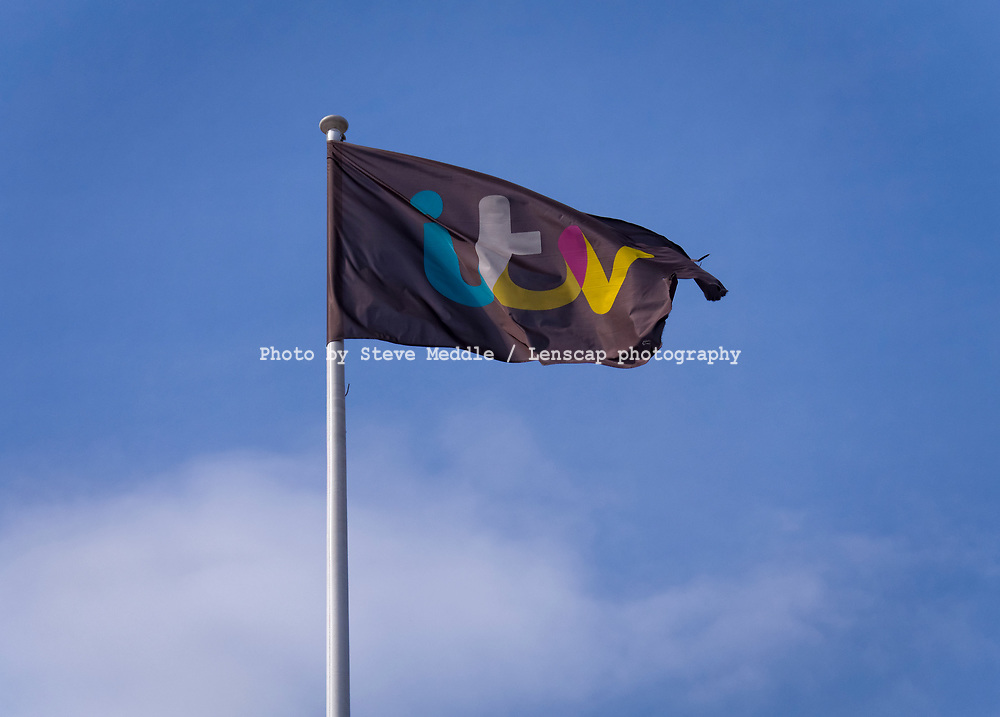 London, England - March 30, 2017:  A Flag bearing the ITV logo flies above ITV Plc Television Studios in London, ITV first launched in 1955.
