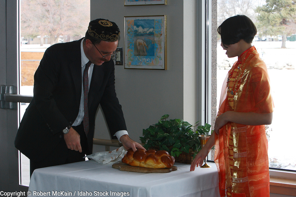 IDAHO. Boise. Rabbi with Asian Jewish girl blessing Challah bread at her Bat Mitzvah. December 2008. #pa080695 MR