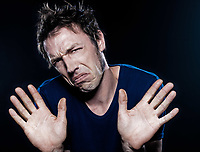 studio portrait on black background of a funny expressive caucasian man frowning refusal deny
