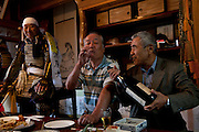 The chairman of the Soma Nomaoi festival Ushitaga Yasumitu (L) having breackfast and a few drinks with friends at his home before the festival starts in Minami Soma