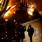 Flames inside a fully-engulfed Westport Presbyterian Church at 201 Westport Road kept Kansas City, Mo. firefighters outside the structure trying to contain the blaze with aerial ladders as bystanders watched and videotaped the damage.