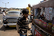 Azharuddin Ismail, 10, the child actor playing the role of 'young Salim', the brother of Jamal, protagonist of Slumdog Millionaire, the famous movie winner of 8 Oscar Academy Awards in December 2008, is buying a local Indian tobacco product for his father on the streets surrounding the slum where he still lives with his family next to the train station of Bandra (East), Mumbai, India. Various promises were made to lift the two young actors (Azharuddin Ismail and Rubina Ali) from poverty and slum-life but as of the end of May 2009 anything is yet to happen. Rubina's house was recently demolished with no notice as it lay on land owned by the Maharashtra train authorities and she is now permanently living with her uncle's family in a home a stone-throw away in the same slum. Azharuddin's home too was demolished in the past two weeks, as it happens every year in his case, as the concrete walls were preventing local authorities to clear a drain passing right behind it. As usual, his father is looking into restoring the walls as soon as the work on the drain has been completed.