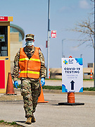 "26 APRIL 2020 - DES MOINES, IOWA: A soldier with the Iowa Army National Guard walks to the gate of the COVID-19 drive through testing site in Des Moines. Iowa started mass testing Saturday, with a drive through testing site in a parking lot in downtown Des Moines. The testing this weekend is considered a ""soft opening"" for the program and tests were reserved for medical professionals and first responders. Despite numerous outbreaks in meat packing plants throughout Iowa, members of the public have not been able to get tested. On Saturday, 25 April, there were 5,092 confirmed cases of COVID-19 (Coronavirus / SARS-CoV-2) in Iowa (an increase of 647 since Friday, April 24) and 112 deaths in Iowa caused by COVID-19.               PHOTO BY JACK KURTZ"