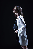 beautiful smiling caucasian pregnant  woman portraitt   touching her belly in nightie on studio isolated black background