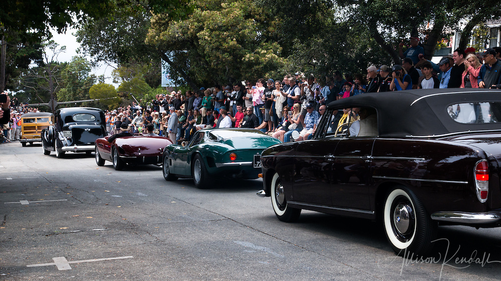Participants in the Pebble Beach Concours d'Elegance event cruise down Ocean Avenue in Carmel-by-the-Sea during the Pebble Beach Tour d'Elegance.