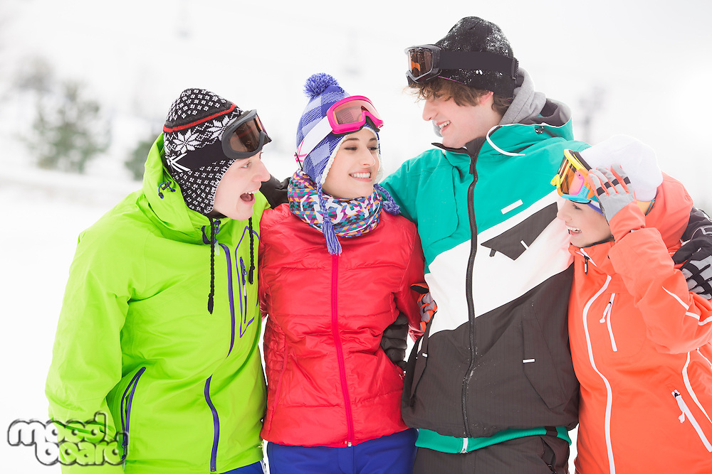 Portrait of young friends standing together in snow