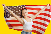 Portrait of happy young woman holding American flag over yellow background