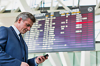 Mature attractive businessman using smartphone while standing against flight display screen in airport