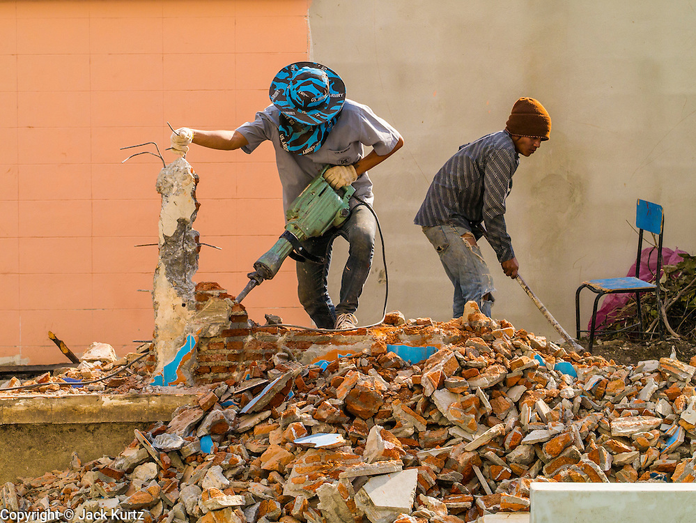28 DECEMBER 2012 - BANGKOK, THAILAND:  Construction workers take apart a concrete wall in front of a school on Sukhumvit Soi 22 in Bangkok. The wall was being torn down to make way for a new wall.     PHOTO BY JACK KURTZ