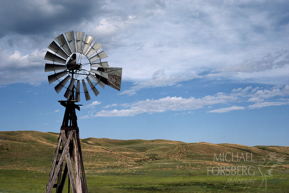 A windmill in the Nebraska Sandhills stands tall over the rolling landscape.