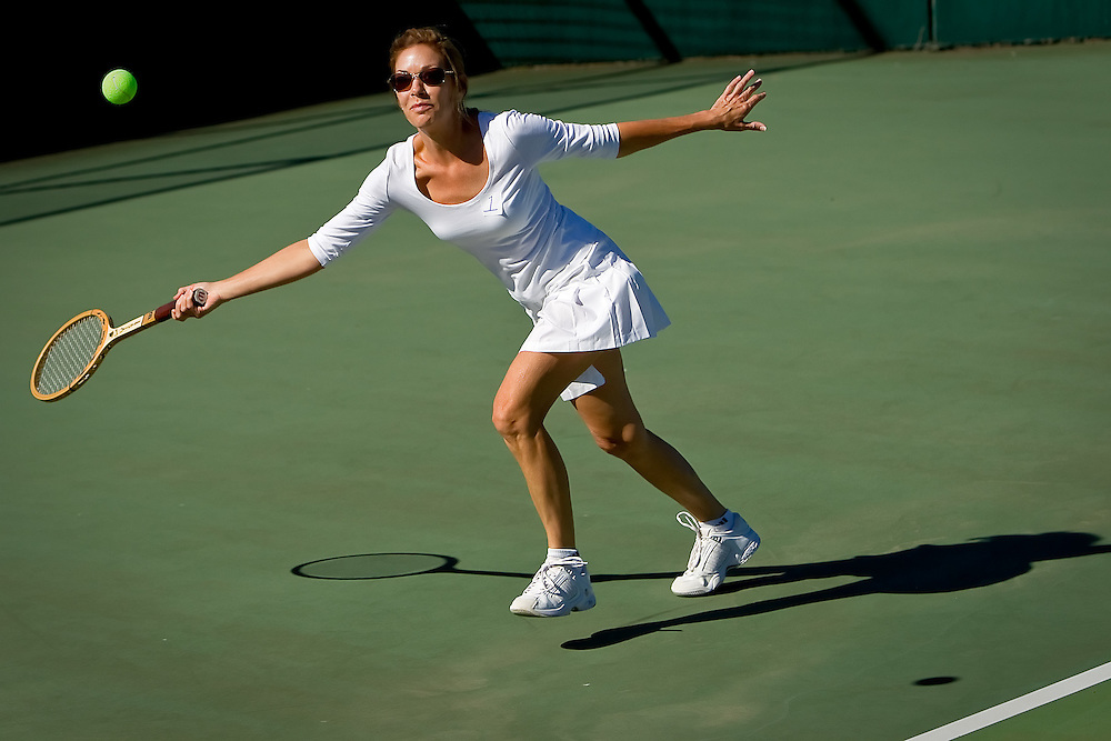 "Amy Hewel lunges to return a ball Monday while playing in the ""woods and whites"" themed ladies tennis invitational at The Coeur d'Alene Resort Golf Course. About 20 women took part in the event donning white tennis outfits and vintage wood tennis rackets."