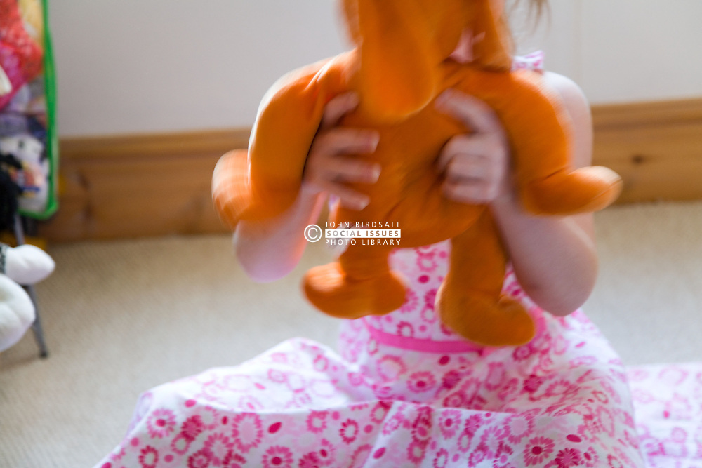 Little girl playing with a soft toy,