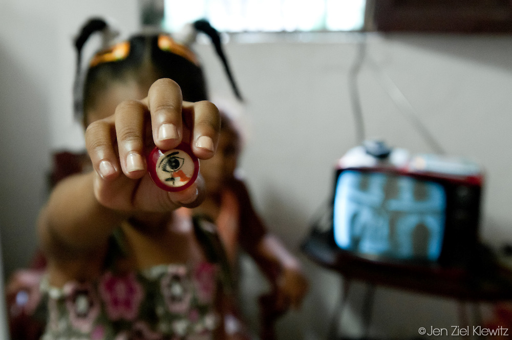 Stefanie Pelegrino, 7, holds up a small charm displaying a symbol believed to ward off the evil eye. The symbol is often worn as an amulet, found hanging in the entryways, or painted on the walls of Cuban homes.  Photo by Jen Klewitz