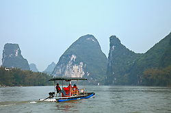 Cruising the River Li, Round-trip Yangshuo, Southern China. Two-six person rafts made of plastic piping and powered by an outboard motor take Yangshuo visitors on a 90-minute cruise.